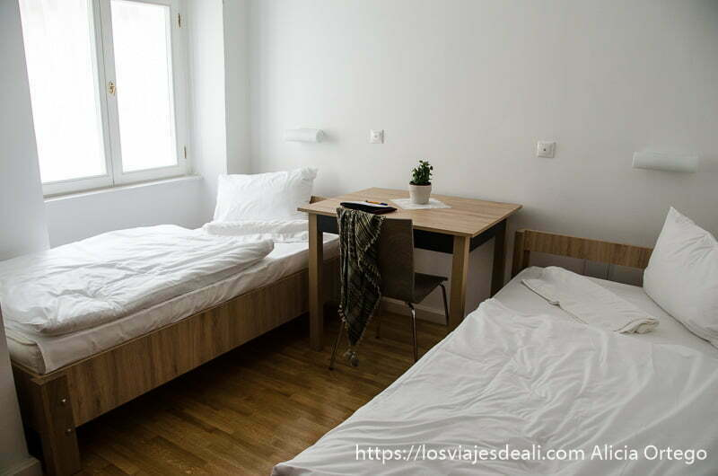 habitación de bed+breakfast con dos camas en blanco y madera en pécs