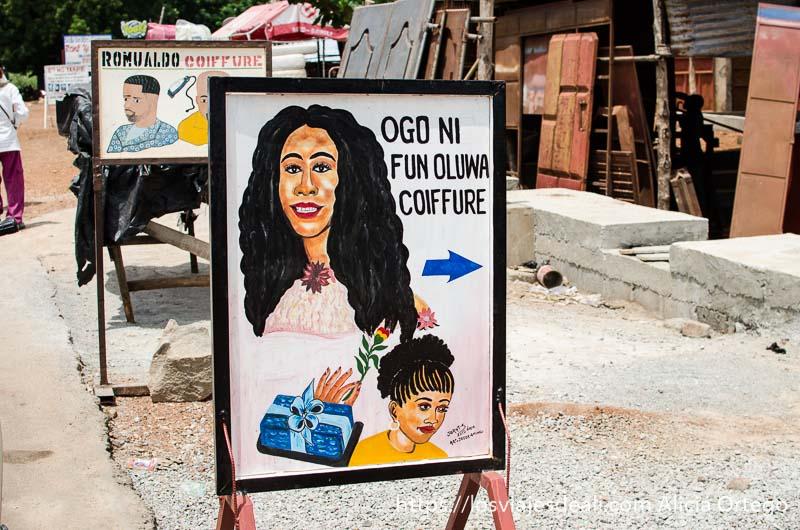cartel de peluquería en la calle con dibujo de mujeres con pelo negro rizado ruta en benin
