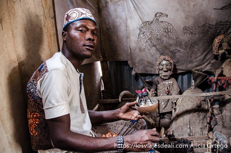 fetichero mirando a la cámara mientras prepara muñecos vudú en la capital de togo