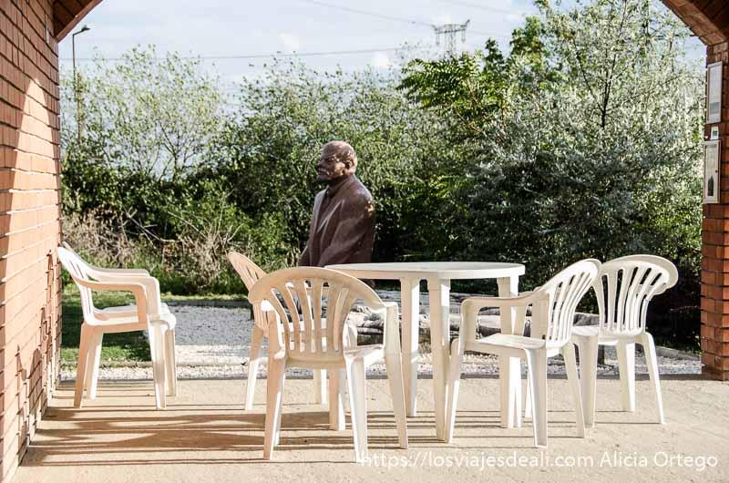 estatua de lenin al fondo y sillas de plástico de terraza en memento park de budapest