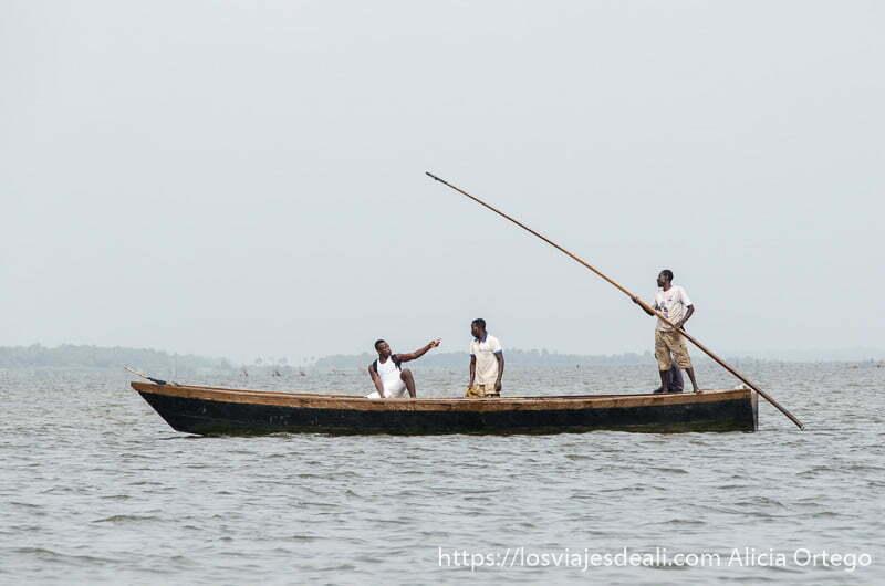 tres hombres en una barca en medio del lago de togoville