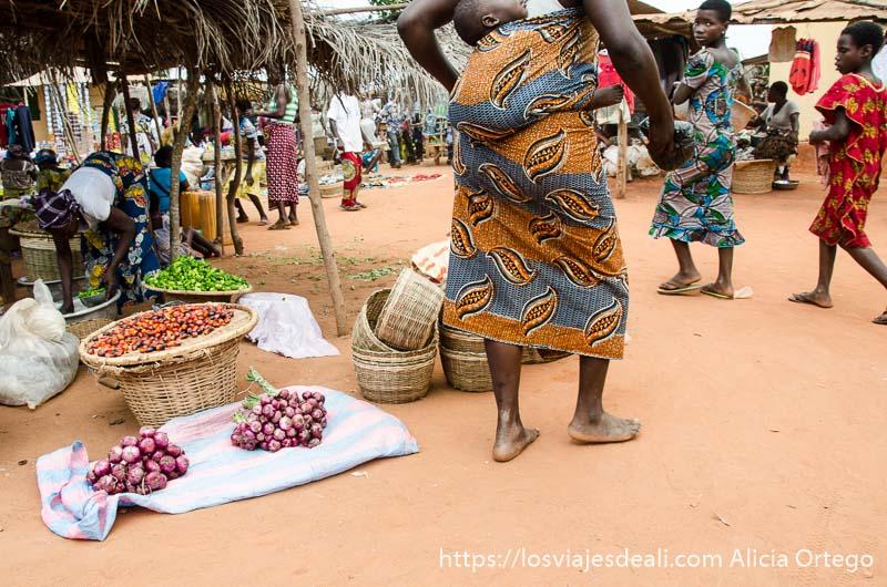 mujer pasando junto a puesto de cebollas en el mercado de togoville