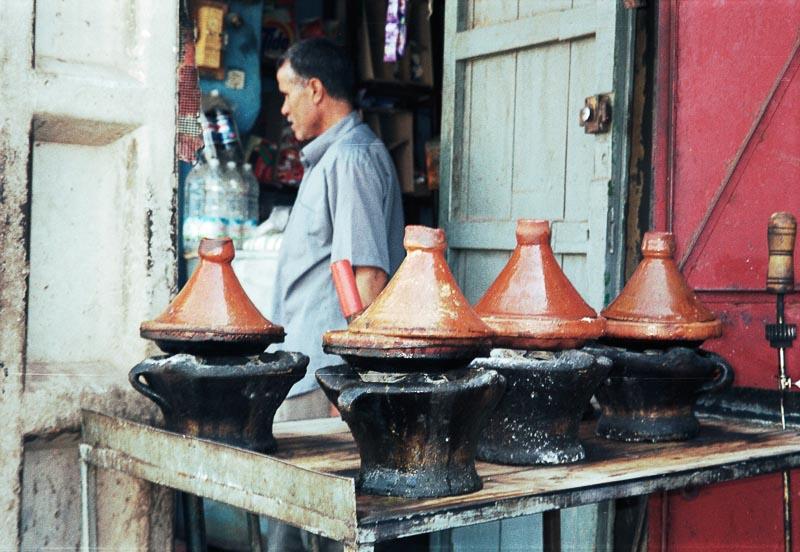 hilera de tajines en el fuego en un puesto de marruecos