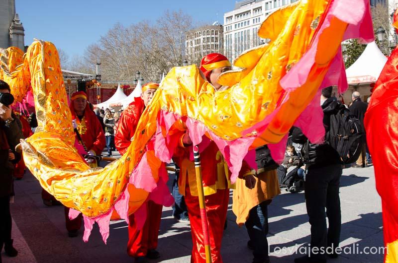 fila de hombres portando dragón de tela de color rojo y amarillo en el año nuevo chino en madrid