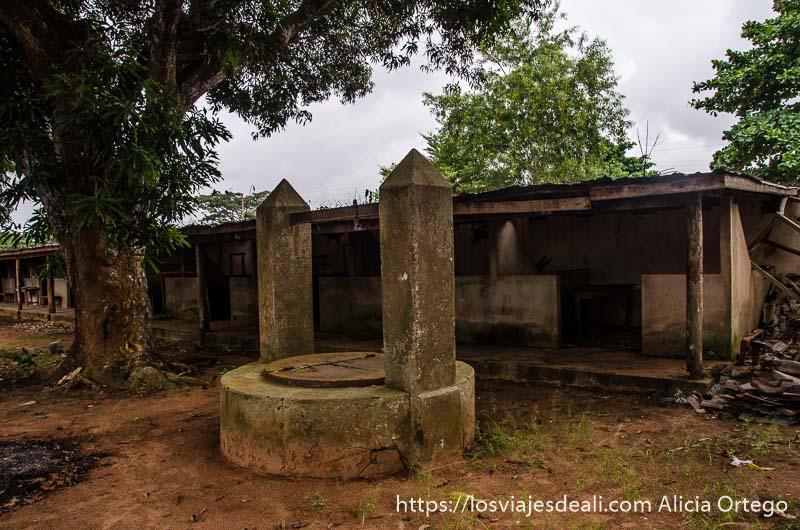 barracones para esclavos con un pozo delante y un gran árbol historia de la esclavitud en benin