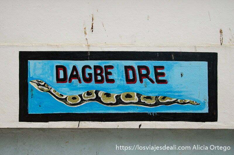 cartel del templo de las pitones de ouidah pintado en una pared con dibujo de serpiente pitón