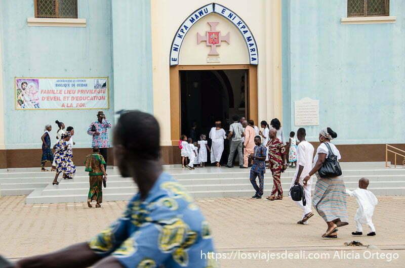 iglesia cristiana de ouidah con gente entrando y un motorista pasando por delante
