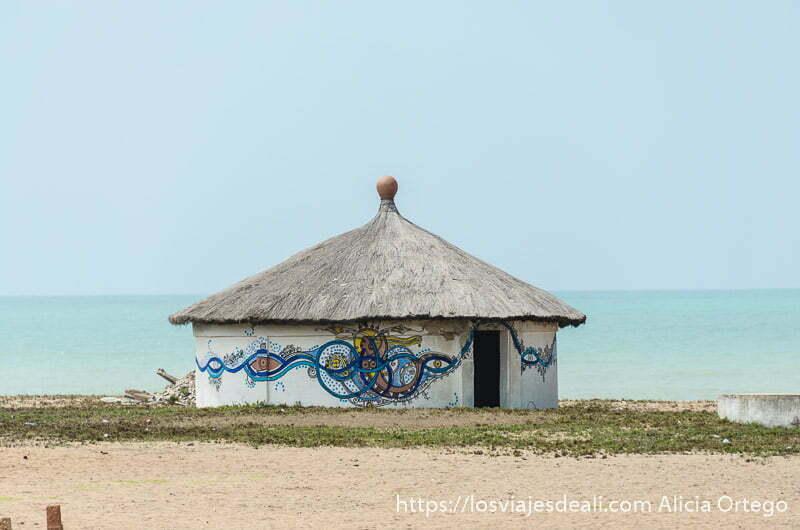 casa redonda y paredes pintadas con serpientes y otras figuras templo vudú en la playa de ouidah