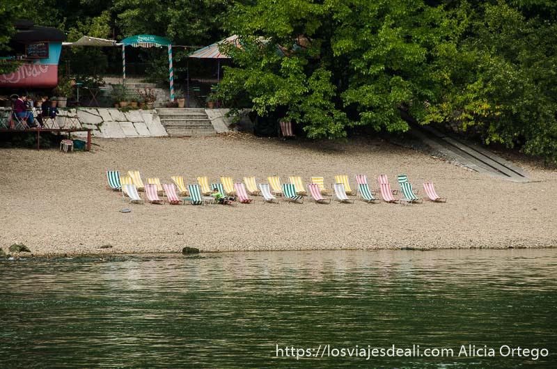 hilera de hamacas de rayas de colores en una playa del danubio volviendo de szentendre