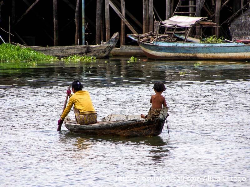 una mujer remando en una barca y su hijo al timón en cam sap excursión cerca de los templos de angkor