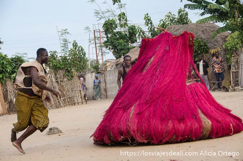 sacerdote saltando al lado de una máscara zangbeto de color rojo en ceremonia vudú de benin