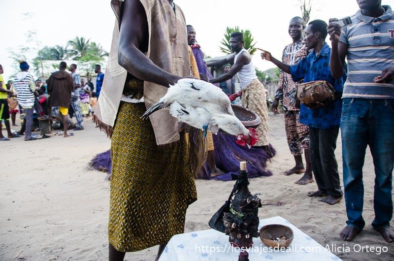 sacerdote con pollo vivo en la mano en la ceremonia vudú