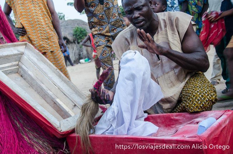 pequeño ataúd rojo con muñeco que se levanta solo a las órdenes del sacerdote en la ceremonia vudú