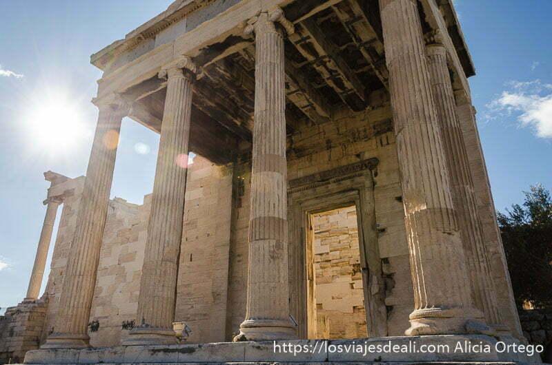 templo con columnas y sol entrando por un lado en la acrópolis de atenas y su museo