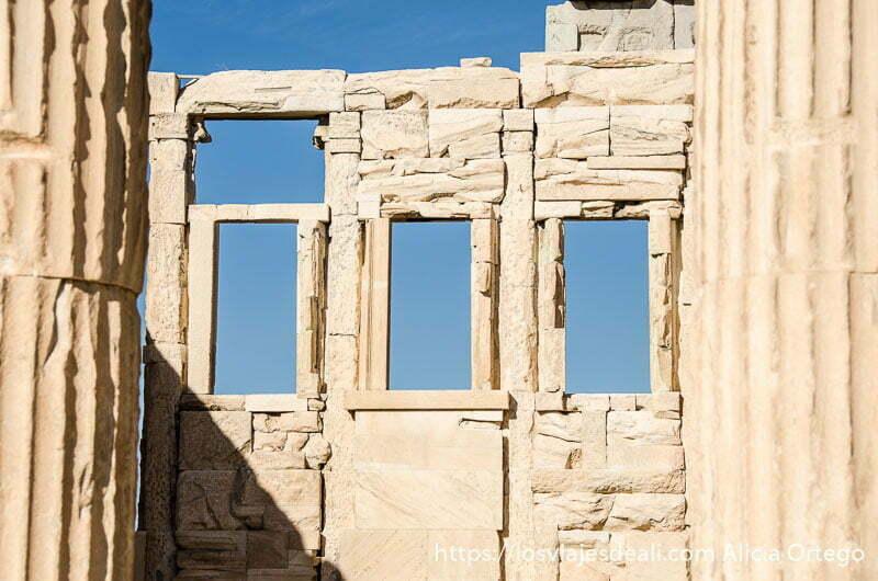tres ventanas en pared de templo con cielo azul detrás acrópolis de atenas