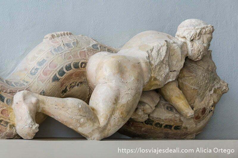 escultura de hombre griego desnudo cabalgando una especie de serpiente gigante con restos de color en el museo de la acrópolis de atenas