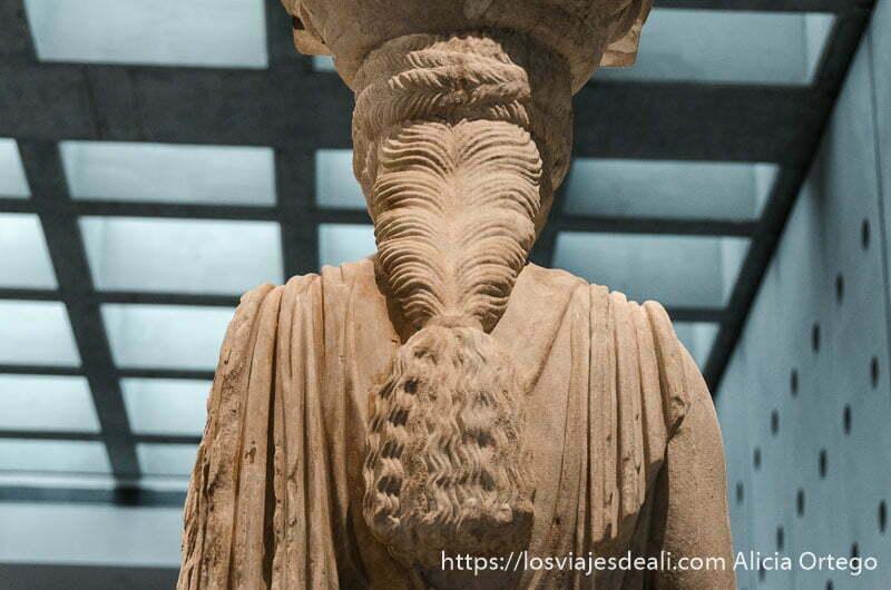 espalda de una cariátide donde se aprecia su peinado ondulado con gran coleta en museo de acrópolis de atenas