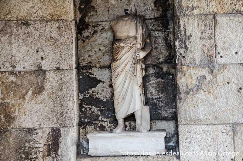 estatua griega sin cabeza en una pared del teatro odeón de Atenas