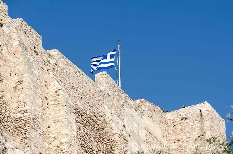 bandera griega ondeando en cielo azul sobre muralla de la acrópolis de atenas