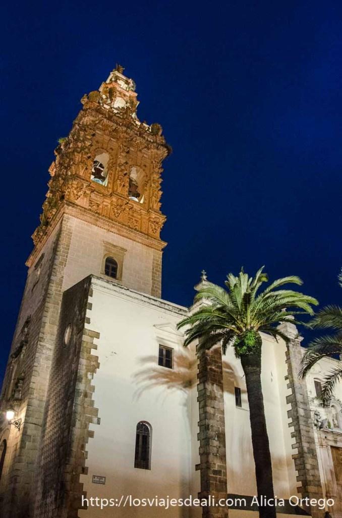 torre de la iglesia de san miguel iluminada por la noche con palmeras junto a la nave central en jerez de los caballeros