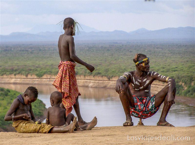 un hombre de la tribu karo sentado en su mini taburete junto a tres niños, y detrás el río Omo
