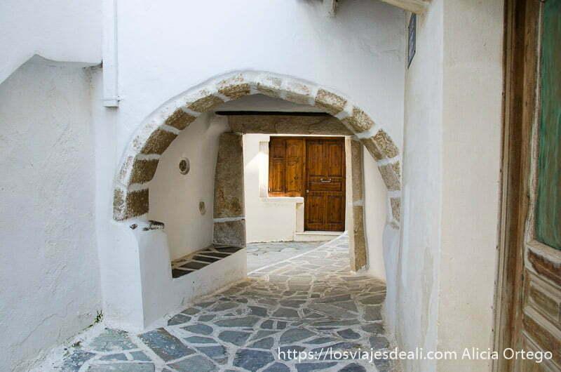 calle blanca con arco de piedra y puerta al fondo en naxos