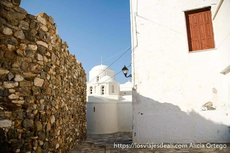 iglesia blanca al fondo de calle con muro de piedra y casa con ventana roja capital de naxos
