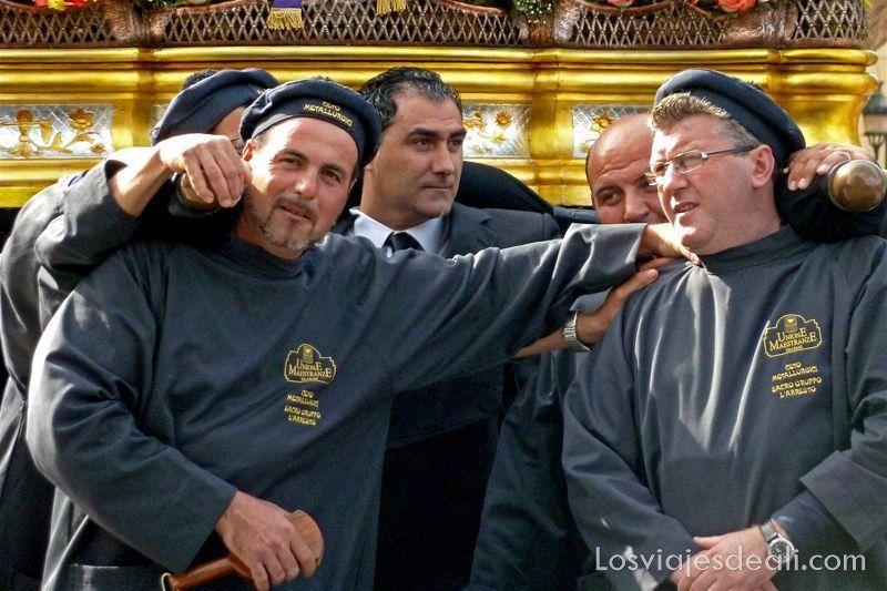 hombres de cofradía junto al paso que llevan en Trápani en semana santa