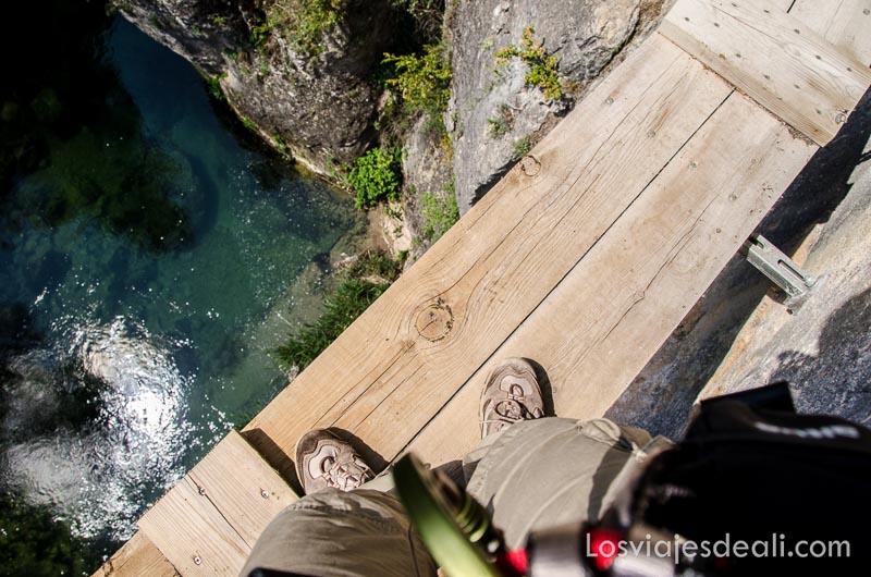 foto de mis pies en pasarela de madera con río debajo fin de semana de actividades en cuenca