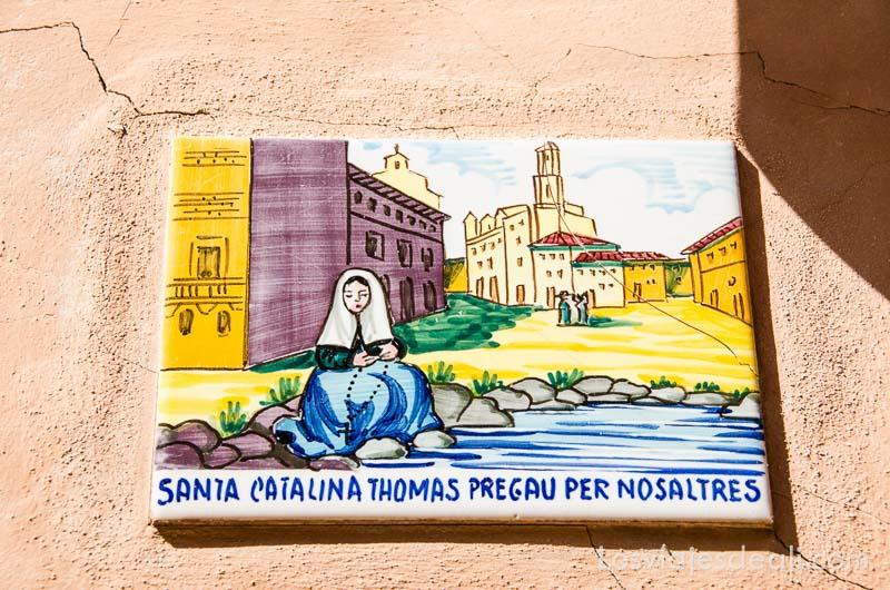 azulejo pintado con escena de santa catalina y pueblo de valldemossa detrás ruta por los pueblos de la tramontana