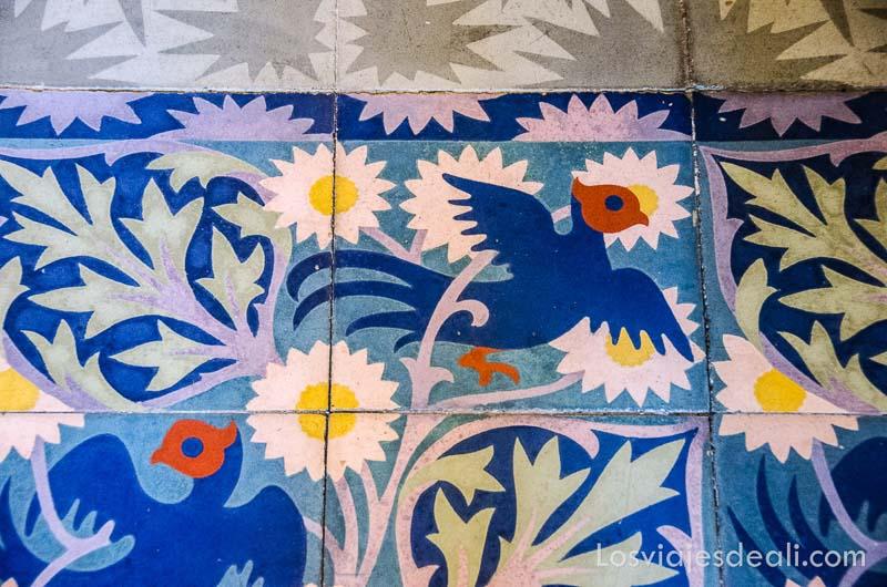 azulejos de suelo con flores y un pájaro pintados de brillantes colores en can prunera de Sóller