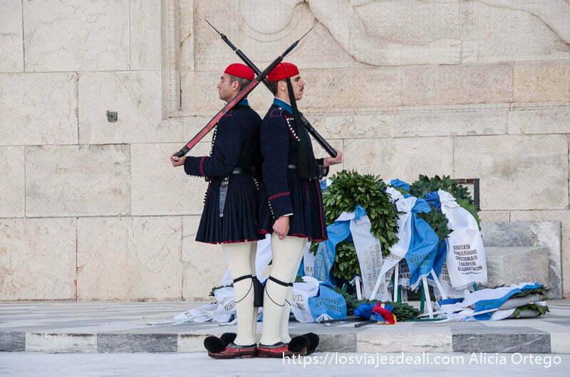 dos soldados espalda contra espalda con su rifle al hombro junto a tumba de soldado desconocido en la plaza de sintagma de atenas