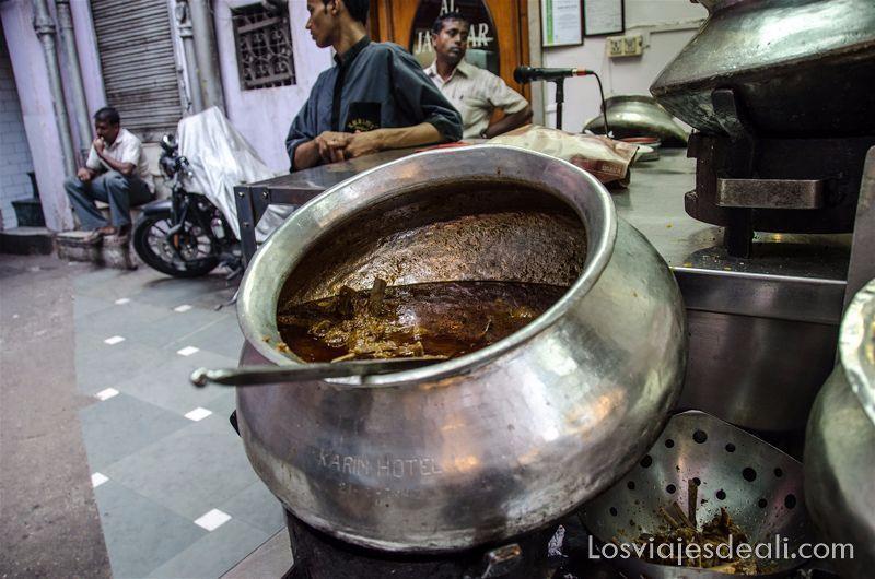 olla de metal llena de cordero en salsa en el Karim's restaurant qué ver en Delhi