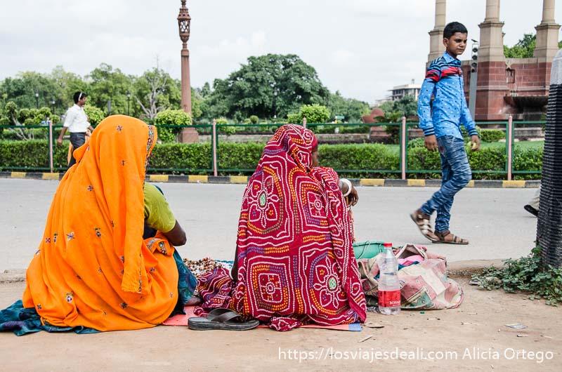 dos mujeres con saris de brillantes colores sentadas en el suelo de un parque qué ver en delhi
