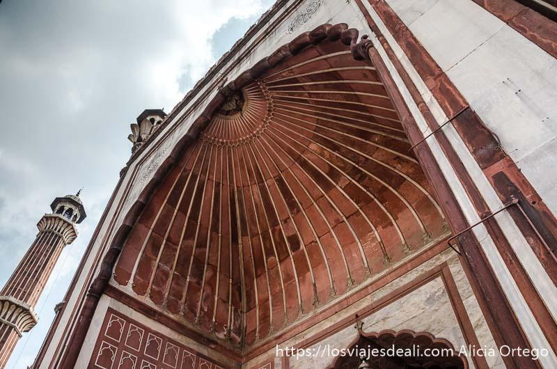 vista desde abajo de gran arcada de entrada de mezquita qué ver en delhi