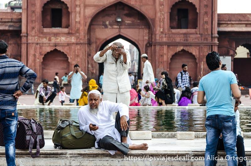 hombre peinándose en el fuente del patio de la mezquita y otro sentado delante de él mirando a cámara qué ver en delhi