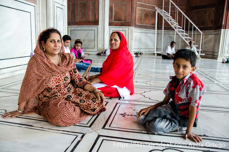 dos mujeres con saris y un niño sentados en el suelo de mármol de la mezquita qué ver en delhi