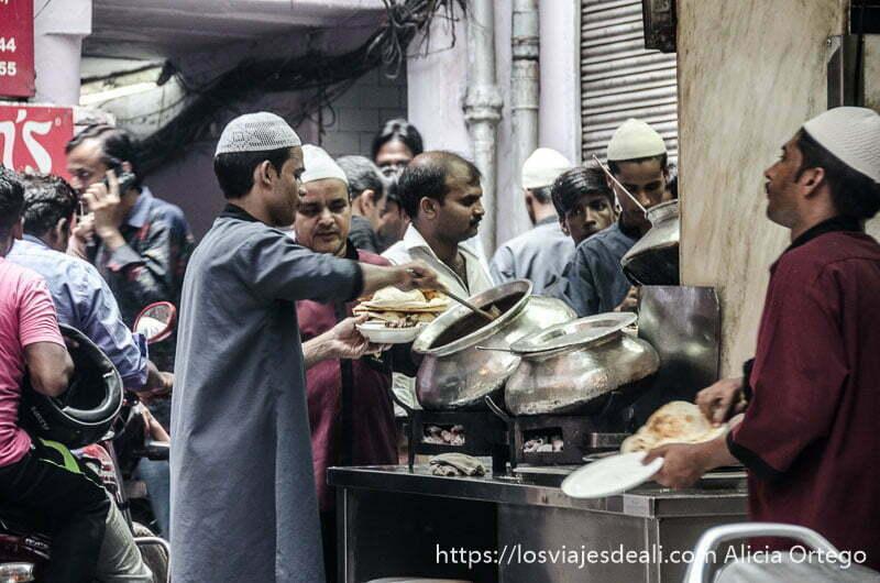 camareros sirviendo comida de las ollas del karim's restaurant en el callejón lleno de gente donde está el restaurante qué ver en delhi