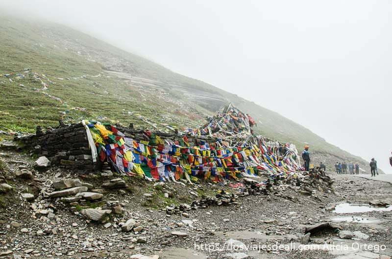 construcción de piedra cubierta de banderas tibetanas de colores bajo cielo de niebla carreteras del himalaya indio