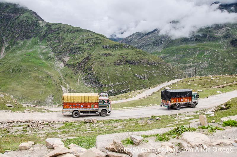 dos camiones coloridos avanzan en las pistas llenas de curvas entre montañas verdes y nubes carreteras del himalaya indio