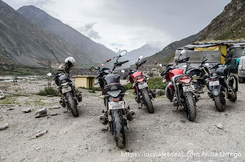 grupo de 6 motos aparcadas frente a paisaje de montaña carreteras del himalaya indio
