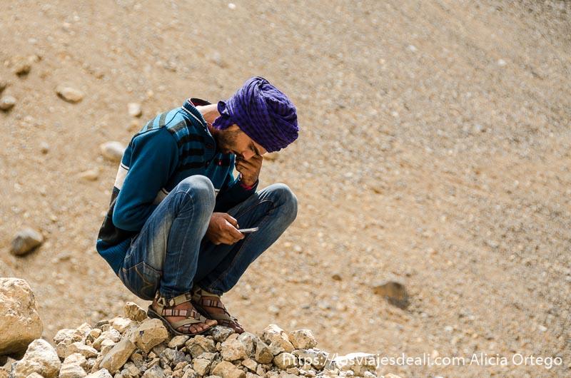 una de las imágenes de india es este joven con turbante morado en cuclillas mirando su móvil carreteras del himalaya indio