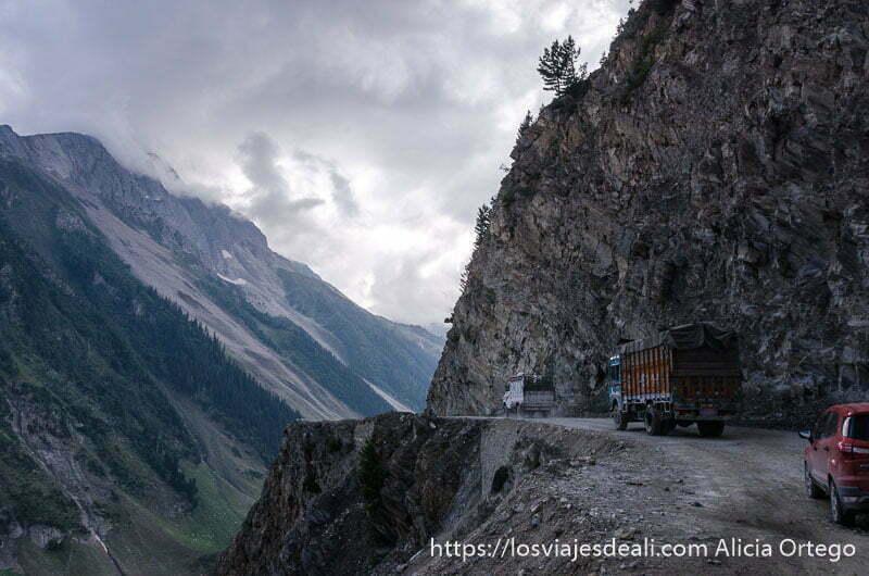 fila de camiones y coches en pista con abismo entre montañas carreteras del himalaya indio