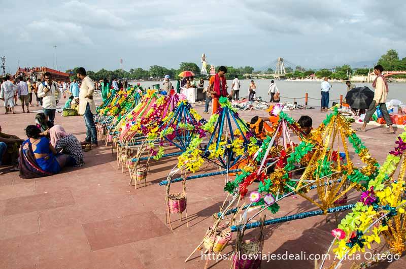 ofrendas de madera y cintas de colores preparadas para tirar al ganges en haridwar