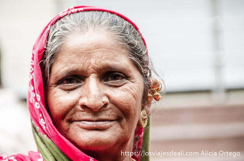 retratos de india.  mujer mayor con sari rojo y pendientes de oro en haridwar