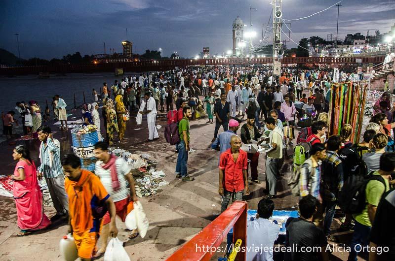 plataformas junto al ganges llenas de gente con la última luz del día y las farolas en haridwar