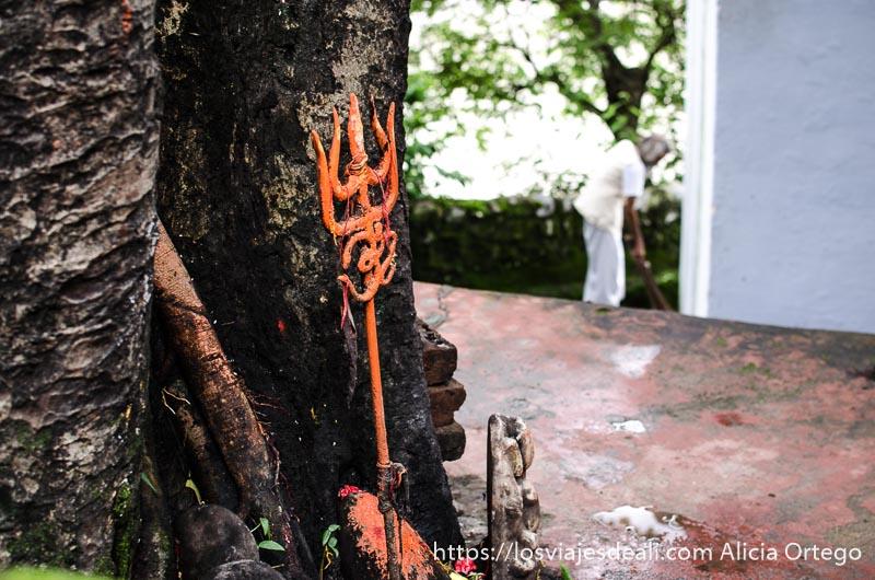tridente de shiva pintado de naranja apoyado en el tronco de un árbol en rishikesh