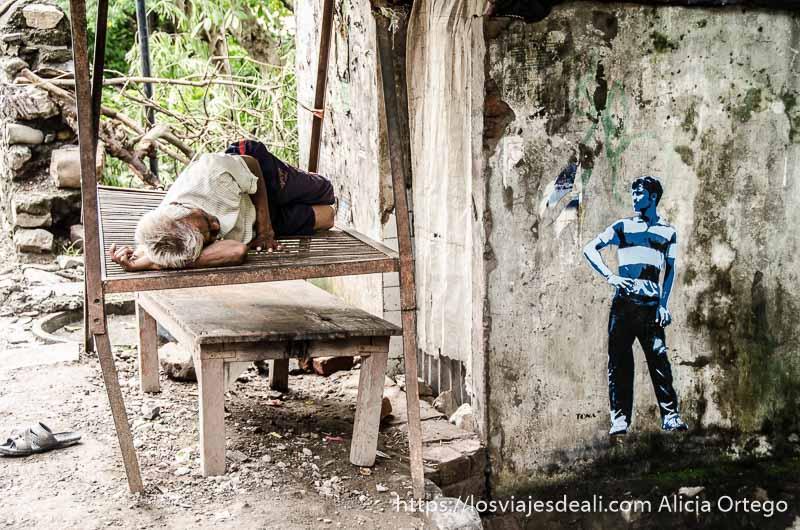hombre durmiendo la siesta en una plataforma de madera y un grafiti de un chico como mirándole en rishikesh
