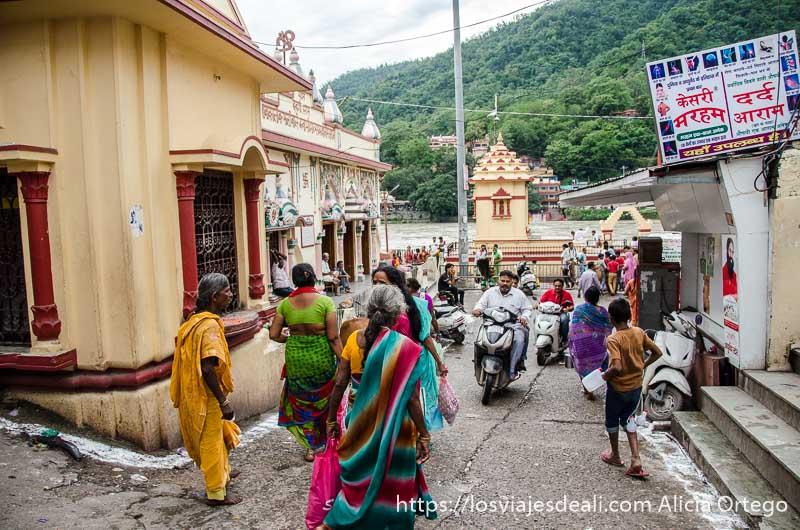 mujeres con sari, motos y vacas por una calle de rishikesh y al fondo el río ganges