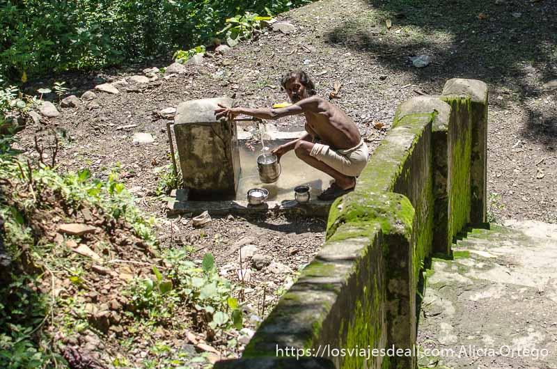 sadhu cogiendo agua de una fuente cerca de rishikesh